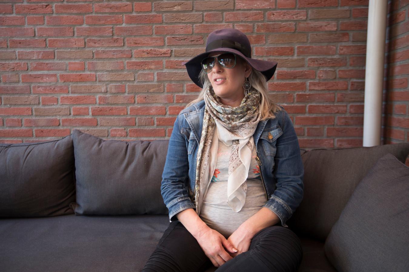 Met hoed en zonnebril op, onder het luifel op haar terras, probeert Madelon Mudde de tropische dagen door te komen.