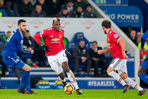 Manchester United's French midfielder Paul Pogba (C) goes past Leicester City's Spanish midfielder Vicente Iborra (L) during the English Premier League football match between Leicester City and Manchester United at King Power Stadium in Leicester, central England on December 23, 2017. / AFP PHOTO / Roland HARRISON / RESTRICTED TO EDITORIAL USE. No use with unauthorized audio, video, data, fixture lists, club/league logos or 'live' services. Online in-match use limited to 75 images, no video emulation. No use in betting, games or single club/league/player publications.  /