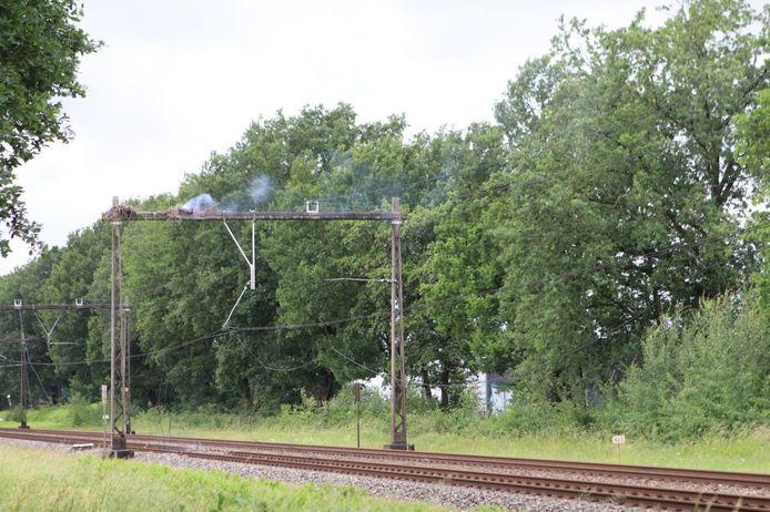 Er komt behoorlijk wat rook van het ooievaarsnest boven het spoor af.
