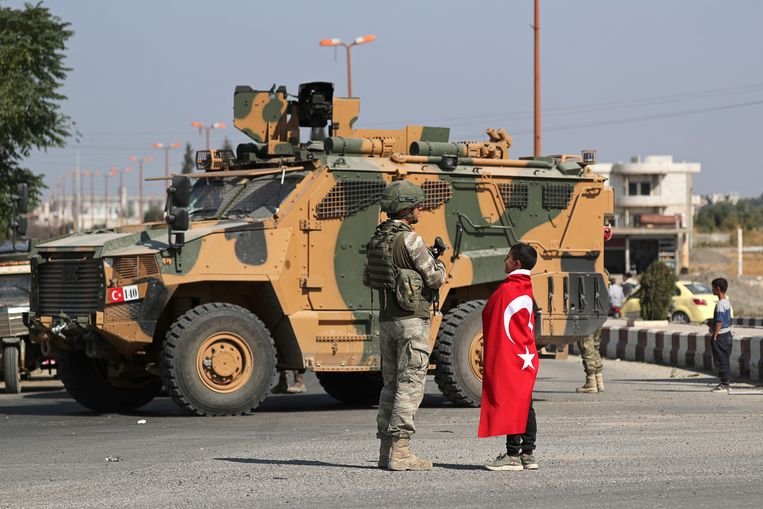 Turkse soldaat met jongen in Tal Abyad, Noordoost-Syrië. Beeld Khalil Ashawi/Reuters