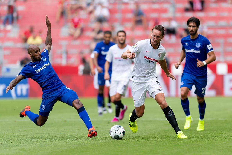Luuk de Jong (midden) strijdt voor Sevilla om de bal met Fabian Delph van FC Everton.