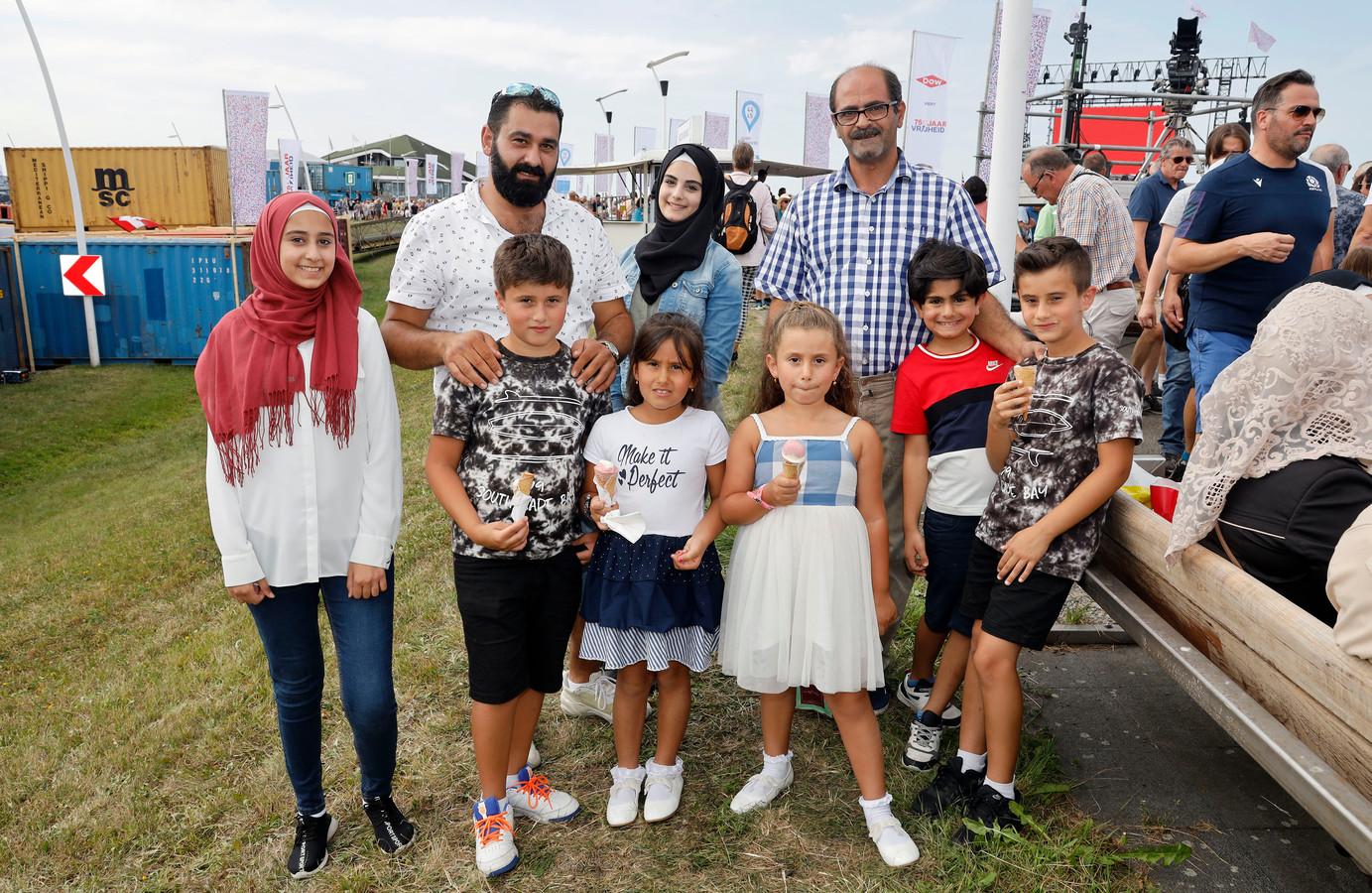 Gevluchte Syrische gezinnen vieren 75 jaar vrijheid mee in Terneuzen, Jehad Kembaz (tweede van links) en Samer Aljani (met geruit overhemd).