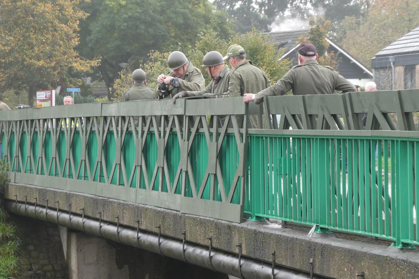 Mannen van hobbyclub Samen Bezig verkleed als militair, bekleden de Gasthuisbrug met houten Bailey-panelen.