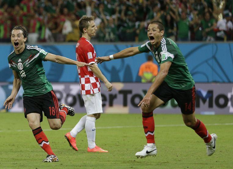 Andres Guardad en Javier Hernandez vieren de tweede goal van Mexico tegen Kroatië. De 'Cruijff van de Balkan', Luka Modric, heeft het er moeilijk mee. Beeld ap