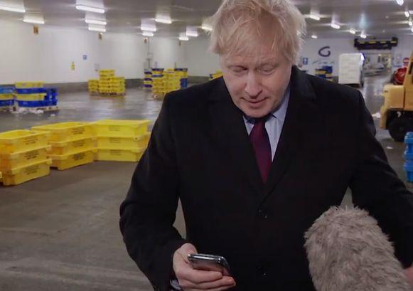 Premier Johnson kon uiteindelijk niet anders dan naar de foto te kijken nadat hij de gsm eerst in zijn zak had gestoken.