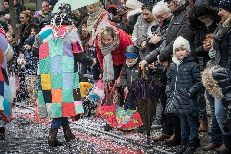 Een paraplu kan je ook perfect gebruiken als snoepenvanger, weet dit knaapje.