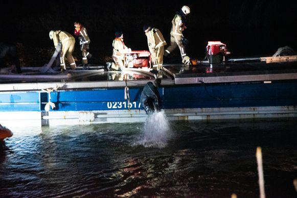 Met zware pompen wordt water uit het lekke schip gepompt.