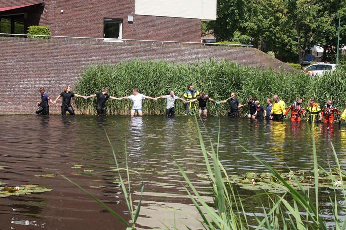 Hand in hand zoeken vrijwilligers in het water in Waalwijk.