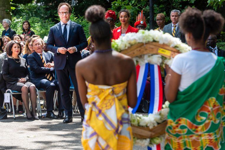 Minister Wouter Koolmees gaat een krans leggen tijdens de herdenking en viering van het einde van de slavernij in Suriname en de Nederlandse Antillen. De herdenking vond plaats bij het Nationaal Monument Slavernijverleden in het Oosterpark. Beeld Hollandse Hoogte /  ANP