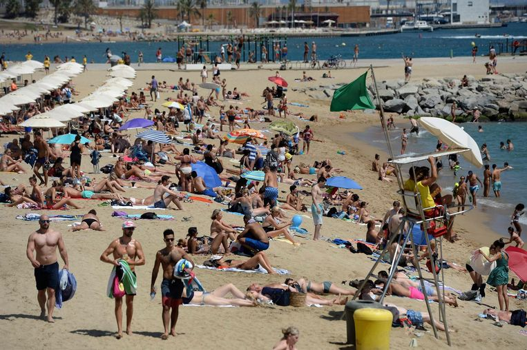 Toeristen op het strand van Barcelona, archiefbeeld ter illustratie.
