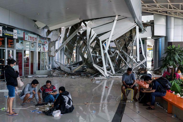 Mensen wachten op het vliegveld van Palu op evacuatie. Ook de luchthaven raakte beschadigd bij de aardbeving en tsunami die vorige week Sulawesi troffen. Beeld Hollandse Hoogte / The New York Times Syndication