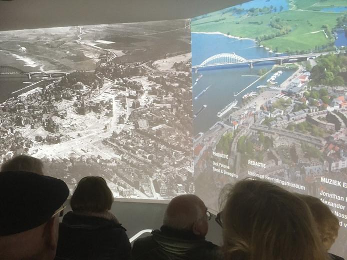 Bezoekers van Infocentrum WO2 kijken in filmzaal De Experience naar het verschil tussen de foto's van Nijmegen na het bombardement van 1944 en het Nijmegen van nu.