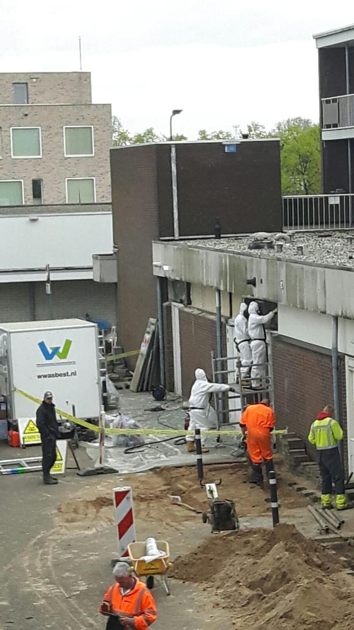 Asbestsanering aan het Van Roosmalenplein, met links de stratenmakers.
