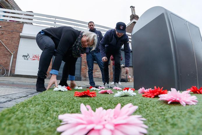 Gemeente Roosendaal start een proef met kunstgras en kunstbloemen naast ondergrondse containers. Wethouder Klaar Koenraad helpt mee bij het plaatsen van de grasmatten bij de drie containers op de hoek van de Dunantstraat en Burgemeester Prinsensingel. Foto: Pix4Profs/Marcel Otterspeer