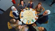 Deelnemers helpen elkaar tijdens bordspel rond armoede