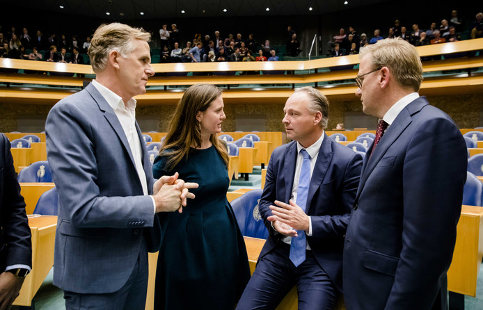 Een onderonsje tijdens het zoveelste Lelystad Airportdebat tussen (vlnr) Lammert van Raan (PvdD), Suzanne Kröger (GroenLinks), Remco Dijkstra (VVD) en Eppo Bruins (ChristenUnie). Een volle publieke tribune kijkt mee.