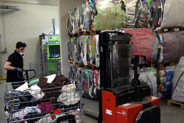 Een medewerker van maatwerkbedrijf Den Azalee in het textielmagazijn.