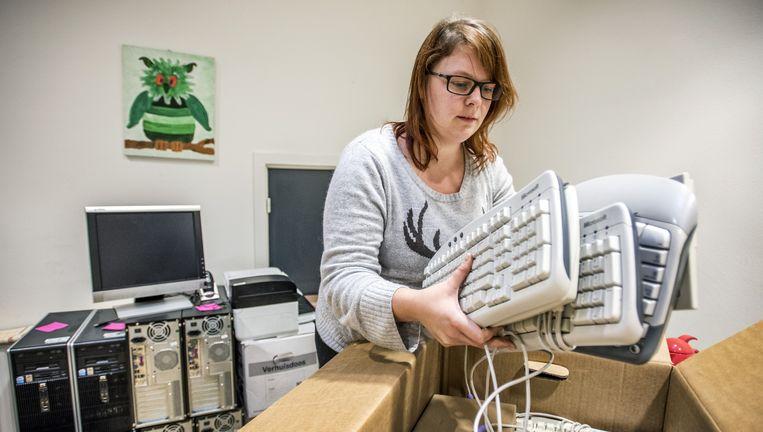 Hilde Lorier van Stichting Leergeld in Utrecht pakt een doos met toetsenborden uit voor haar cliënten. Beeld Raymond Rutting / de Volkskrant