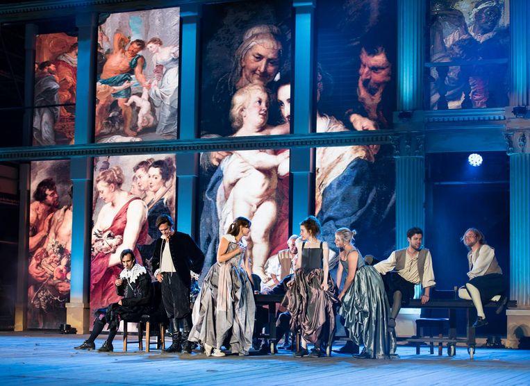 De acteurs in actie met daarachter de ledmuur met projecties van schilderijen.