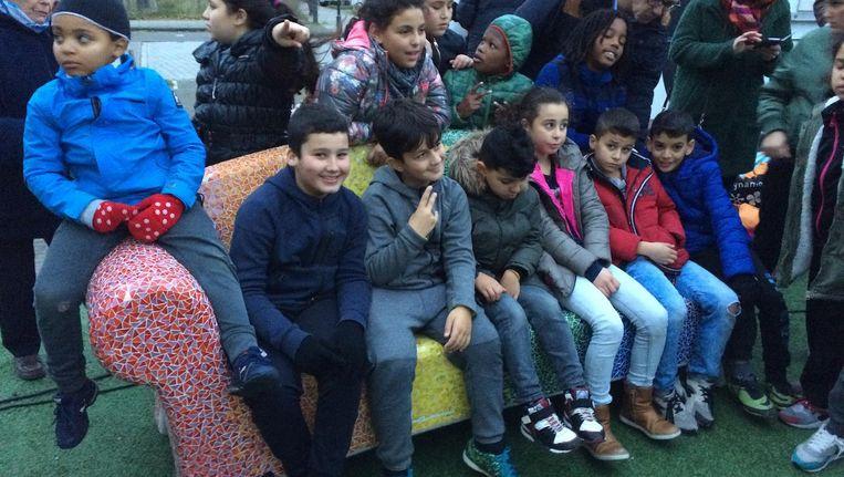 Kinderen vermaken zich op de nieuw geplaatste regenboogbank. Beeld Bart Nauta