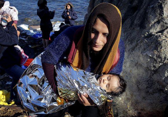 Een Afghaanse migrant draagt haar baby het eiland Lesbos op. Archieffoto uit 2015.