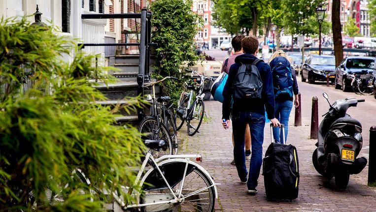 Toeristen lopen met hun koffers over de Amsterdamse grachten. Beeld null