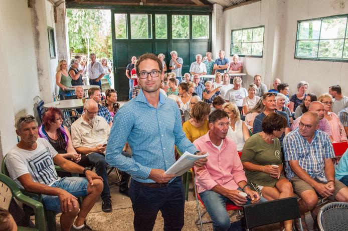 Mark Rotteveel van het Bewonerscollectief Middelburgseweg e.o. in een afgeladen schuur met belangstellenden.