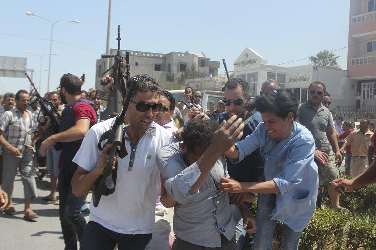 Politieagenten houden woedenende omstaanders in bedwang terwijl een man, vermoedelijk een van de daders van de aanslag, wordt weggeleid.
