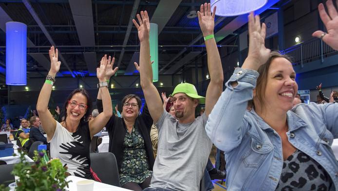 Doven en slechthorenden steken hun handen in de lucht als applaus bij een optreden op het feest van Werelddovendag.