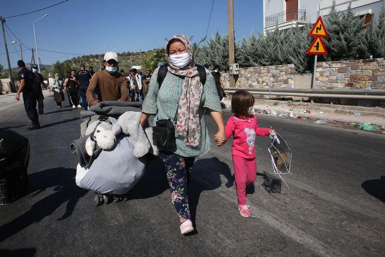 Vluchtelingen sjouwen hun bezittingen rond in de buurt van het afgebrande kamp Moria.  Beeld EPA