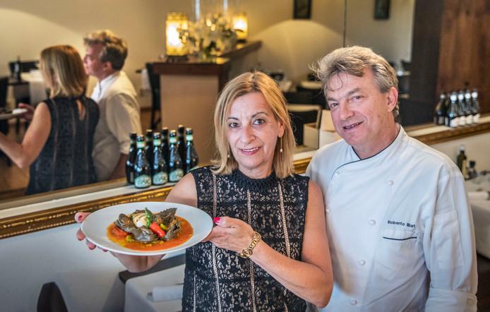 Eigenaresse Sonia Aresu met een bord ravioli nero di sepia. Rechts chef-kok Roberto Illaria.