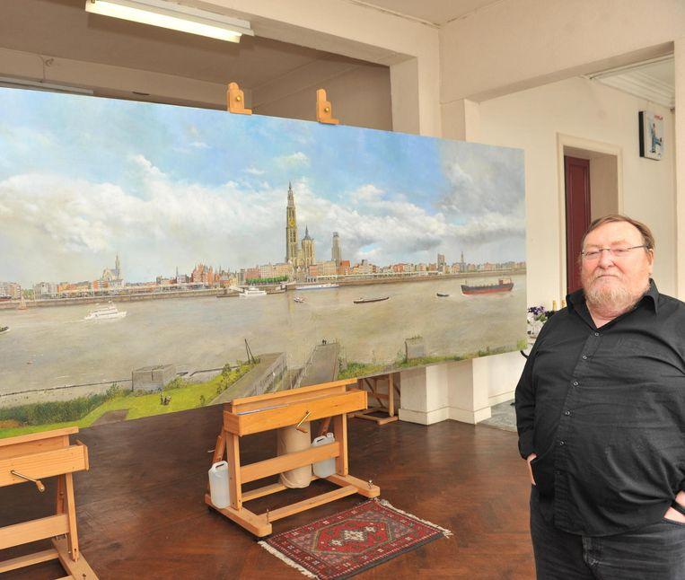 Kunstschilder Willem Dolphyn bij een groot panoramisch zicht van de Antwerpse skyline.