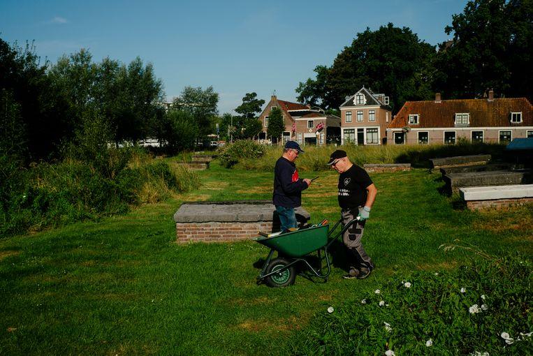 Vrijwilligers bezig met het onderhoud. Beeld Marc Driessen