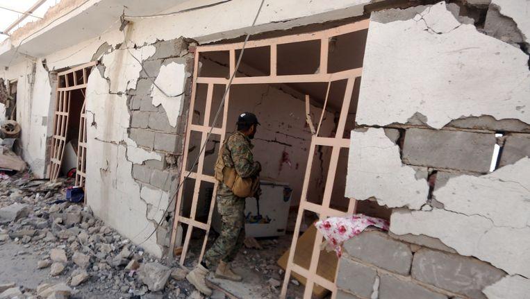Een Irakese sjiïtische strijder inspecteert een verwoest gebouw dat door IS als uitvalsbasis werd gebruikt. Beeld ANP