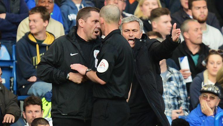 José Mourinho (r) maakt zich kwaad over een beslissing van arbiter Mike Dean (m).