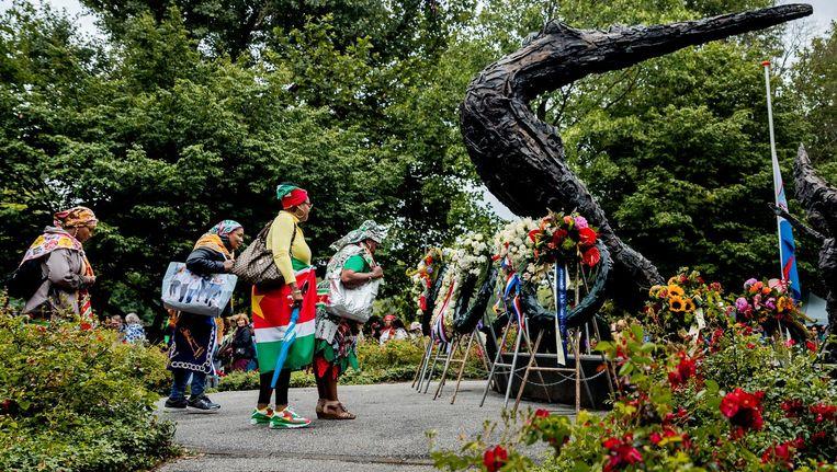 Bezoekers bij het Nationaal Monument Slavernijverleden tijdens de nationale herdenking van de afschaffing van de slavernij in het Oosterpark in 2017. Beeld anp