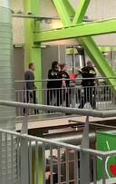 De student wordt meegevoerd door drie agenten.