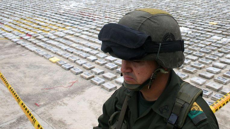 Een Colombiaanse agent bij een eerder in beslag genomen partij cocaïne. Beeld AFP