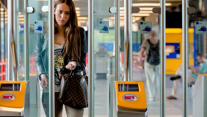 Een reiziger loopt door een toegangspoortje op een NS-station