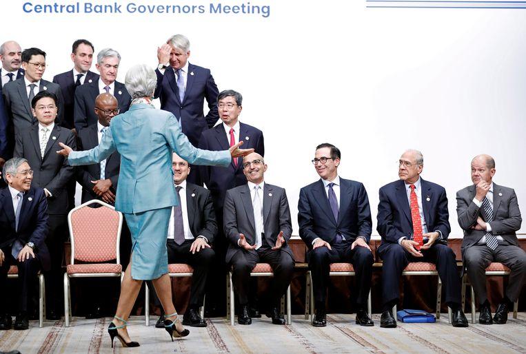 Christine Lagarde, directeur van het IMF rangschikt de de financiële kopstukken die klaarzitten voor de groepsfoto van de G20-ministers van financiën en de centrale-bankpresidenten die waren verzameld voor een vergadering in Fukuoka, Japan. Aanwezig waren onder meer de Amerikaanse Steven Mnuchin (tweede van rechts), en de Duitse Olaf Scholz (uiterst rechts). Beeld REUTERS