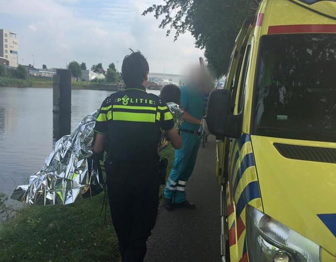 Een agent tilt het jongetje naar de ambulance.