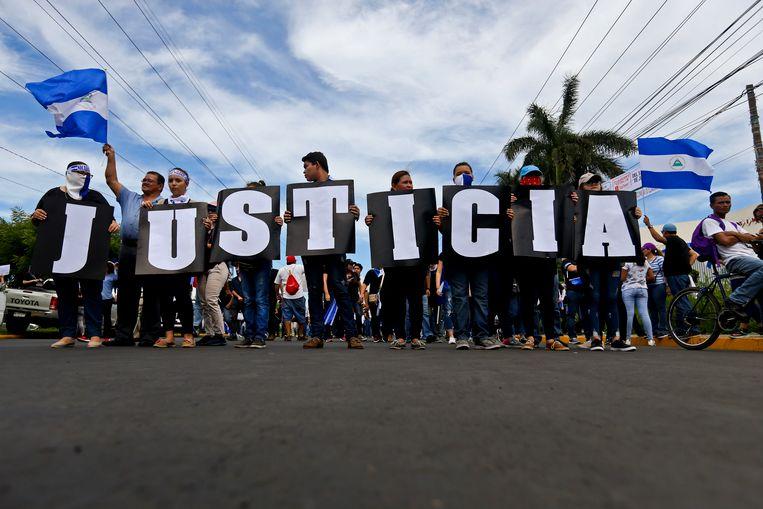 Mensen proberen met borden die het woord 'justicia', 'rechtvaardigheid' vormen in het Spaans.