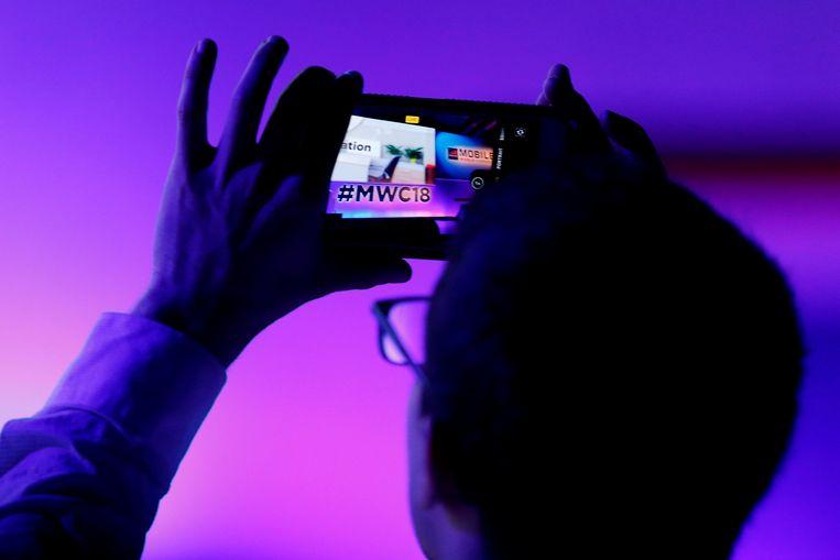 Iemand maakt een foto met zijn smartphone tijdens een persconferentie op de tweede dag van het Mobile World Congress in Barcelona, dat nog tot donderdag loopt.