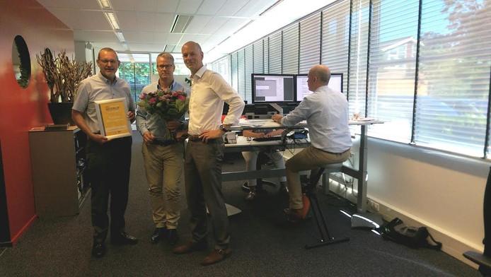 Veldhuis Advies krijgt een oorkonde en een bos bloemen voor de tweede prijs met op de achtergrond het verstelbare meubilair.