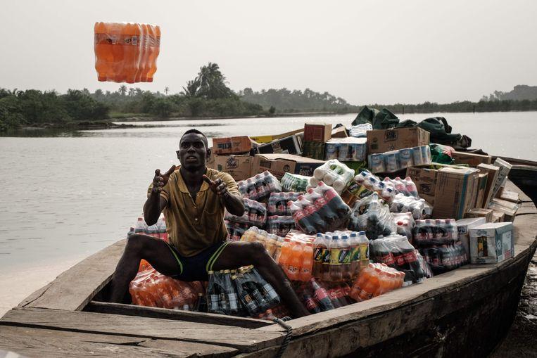 Een Nigeriaanse man ontvangt frisdrank aan de oever van de met Shell-olie vervuilde rivier Bodo in Nigeria. Shell is sinds 2011 betrokken bij een corruptiezaak in Nigeria.  Beeld AFP