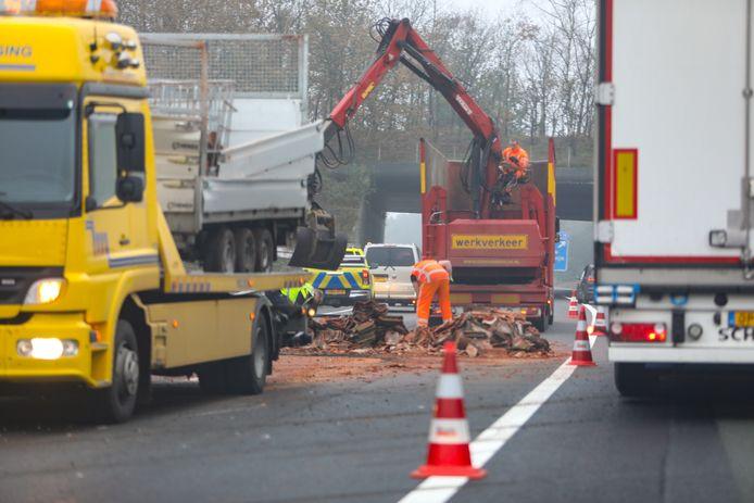 Opruimwerkzaamheden op de A1 nadat een aanhanger met dakpannen is gekanteld.
