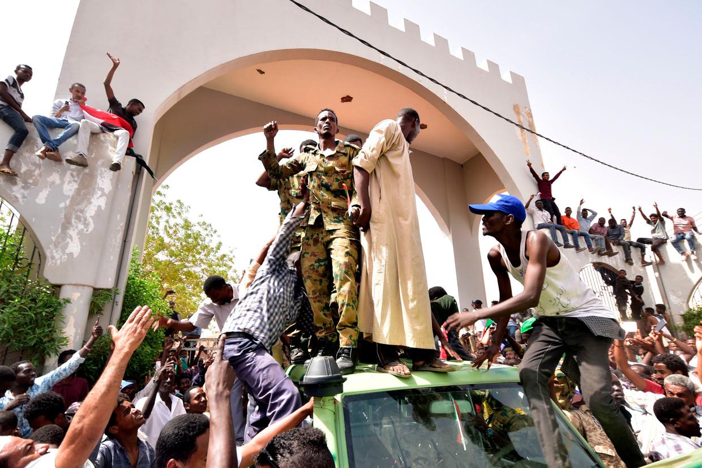 Vreugde Soedanese betogers uiten hun blijdschap over de arrestatie van de afgezette president Omar al-Bashir. Beeld AFP