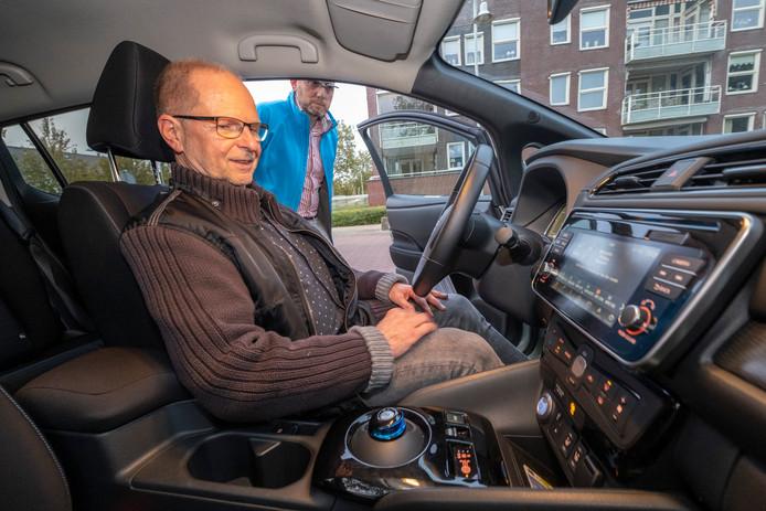 Sjoerd de Jong van Duurzame Mobiliteit Zeeland geeft uitleg aan Walter Zierden over het gebruik van een elektrische auto