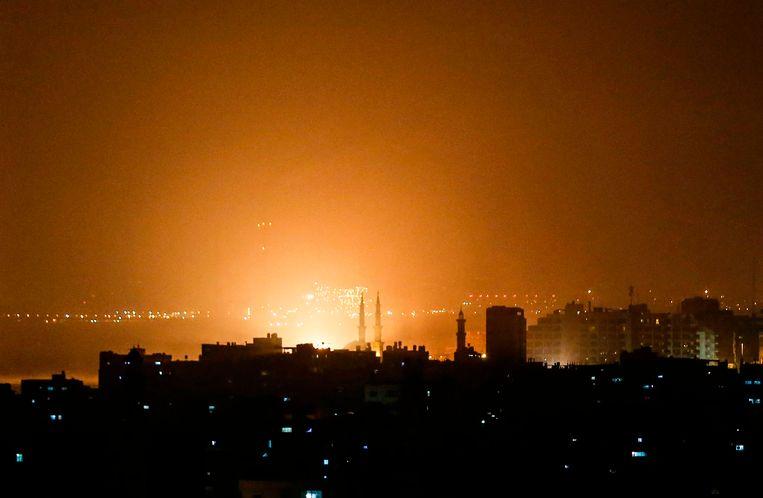 De lucht boven Gaza kleurt oranje gedurende de Israëlische luchtaanval van donderdagavond. Beeld AFP