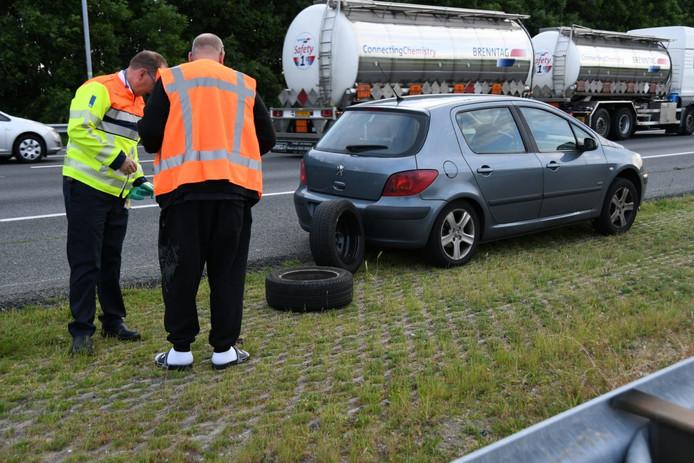 De onfortuinlijke bestuurder (r) bij zijn auto, langs de A12 bij Woerden.